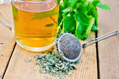 Herbal tea with mint in mug with strainer on board — Stock Photo