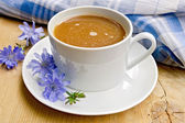 Chicory drink in white cup with napkin on board — Stock Photo