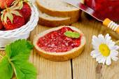 Bread with strawberry jam and chamomile on board — Stock Photo
