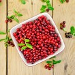 Lingonberry red with leaves in bowl on board — Stock Photo #68137715