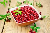Lingonberry red in bowl on board — Stock Photo