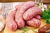 Sausages pork on board with knife — Stock Photo