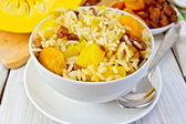 Pilaf fruit with pumpkin in bowl and spoon on board — Stock Photo