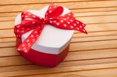 Gift in the form of heart tied with red ribbon with a bow on woo — Stock Photo