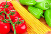 Close-up spaghetti pasta, ripe tomatoes and green peppers on woo — Stock Photo