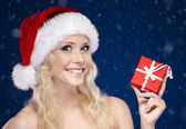 Pretty woman in Christmas cap hands present — Stock Photo