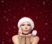 привлекательная женщина в рождество шапка дует поцелуй — Стоковое фото