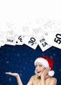 Pretty woman in Christmas cap shows seasonal discount on gifts — Stock Photo