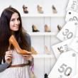 Young woman keeping high heeled shoe on sale — Stock Photo #59095703