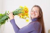 Beautiful woman holding yellow flowers — Stock Photo