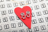 Statuettes hanging on red heart — Stock Photo