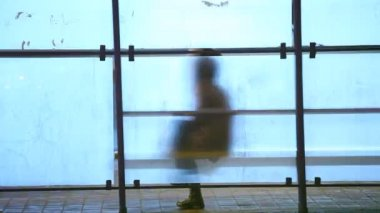 A man sitting on a bus stop waiting — Stok video