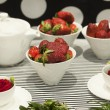 Strawberries and tea on porcelain teapot — Stock Photo #69385085