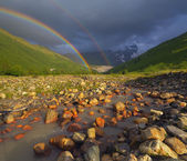 Rainbow over the mountain river — Стоковое фото