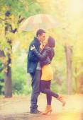 Couplewith umbrella kissing outdoor in the park — Stock Photo