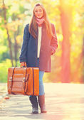 Teen girl with suitcase at autumn outdoor — Stock Photo