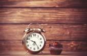 Reloj con alarma y magdalena. — Foto de Stock
