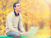 Programmer with notebook sitting in autumn park — Stock Photo