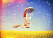 Red-haired girl fly with umbrella over rape field and bubbles ar — Stock Photo