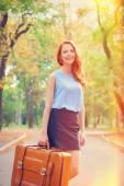 Szczęśliwy rude dziewczyny z walizka w parku jesień. — Zdjęcie stockowe