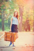 Happy redhead girl with suitcase in the autumn park. — Foto de Stock