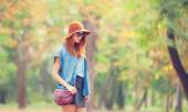 Redhead girl in sunglasses and hat in the autumn park. — Foto de Stock