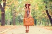 Рыжая девушка с чемоданом в Осенний парк. — Стоковое фото