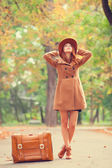 Redhead girl with suitcase in the autumn park. — Stock Photo