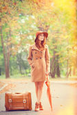Redhead girl with umbrella and suitcase in the autumn park. — Stock Photo