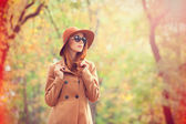 Redhead girl in sunglasses and hat in the autumn park. — Stock Photo