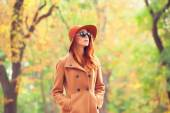 Redhead girl in sunglasses and hat in the autumn park. — 图库照片