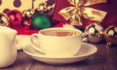 Cup of coffee and gifts at background — Photo