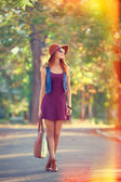 Beautiful redhead girl with bag in the park. — 图库照片