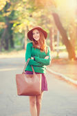 Redhead girl in hat in the autumn park. — Stock Photo