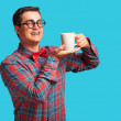 Nerd with cup of coffee on blue background. — Stockfoto #52839701