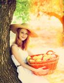 Beautiful redhead girl with fruits in basket at garden. — Stock Photo