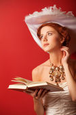Portrait of redhead edwardian women with book on red background. — 图库照片