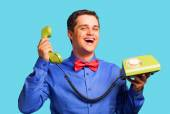 Happy man with green telephone on blue background — Stock Photo