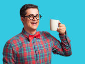 Nerd with cup of coffee on blue background. — Stock Photo