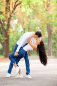 Teen couple kissing in the park in autumn time — Stock Photo