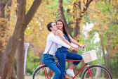 Teen couple with retro bike kissing in the park in autumn time — Foto de Stock
