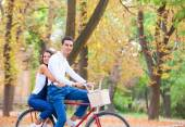 Teen couple with bike in the park in autumn time — Stok fotoğraf