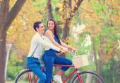 Teen couple with bike in the park in autumn time — Stock Photo