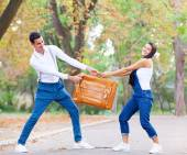 Teen couple with retro suitcase in the park in autumn time — Stock Photo
