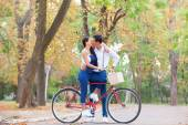 Teen couple with retro bike kissing in the park in autumn time — Stock Photo