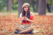 Beautiful brunette girl with cup in the park. — Stock Photo