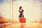 Beautiful brunette girl with suitcase on the countryside road. — Stock Photo
