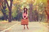 Beautiful brunette girl with suitcase in the park. — Stock Photo