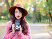 Beautiful redhead women with camera in autumn park. — Stock Photo