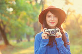 Brunette girl with camera in the park in sunset time — Stock fotografie